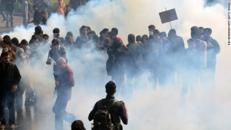 Demonstrators react from tear gas fired by police during a protest calling for better safety for women. New Delhi alone reported 572 rapes last year and more than 600 in 2012.