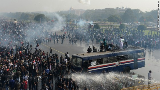 Police spray water and fire tear gas towards demonstrators.