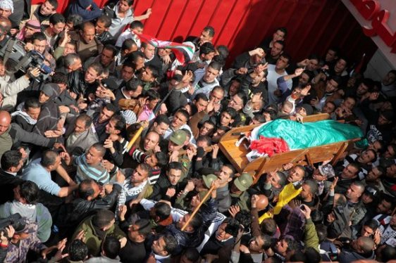 The body of Arafat Jaradat (C) is carried through the West Bank town of Saeer, near Hebron, prior to his funeral on 25 February 2013. Thousands attended the funeral of Arafat Jaradat, 30, whose death in an Israeli jail on 23 February sparked riots across the Israeli-occupied West Bank.