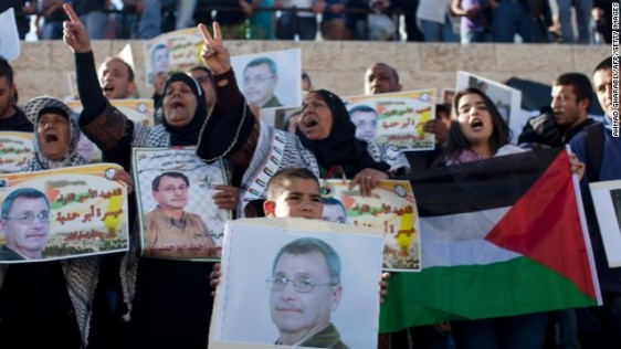 Palestinian protesters hold up photos of Maisara Abu Hamdiyeh, a prisoner who died of cancer while in an Israeli jail.