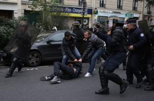 Anti riot police officers arrest a man as high school students demonstrate in Paris, on October 18, 2013, in protest against the deportation of foreign pupils following the high-profile eviction of a 15-year-old Roma girl (AFP Photo / Kenzo Tribouillard)